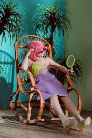 fashionable young female model in pink wig sitting in rocking chair and looking at mirror