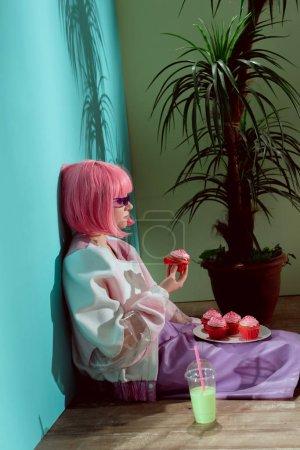 Photo pour Vue latérale d'une fille élégante perruque rose, manger des gâteaux tout en étant assis sur le plancher - image libre de droit