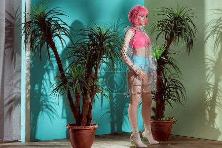 beautiful female model in pink wig and transparent raincoat posing in studio