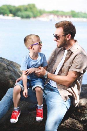 Photo pour Heureux père et fils se regardant sur des pierres près de la rivière - image libre de droit