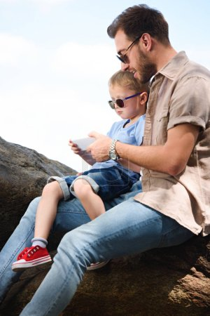 father and son using smartphone on stones at park
