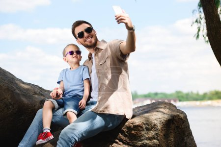 father and son taking selfie with smartphone at park