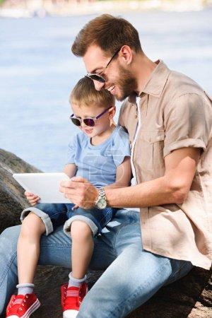 Photo pour Père et fils utilisant tablette près de la rivière au parc - image libre de droit