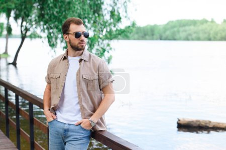 handsome man leaning on railing near lake at park