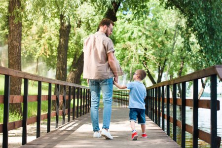 back view of father and son holding hands and walking on bridge at park