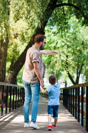 back view of father and son pointing on something on bridge at park