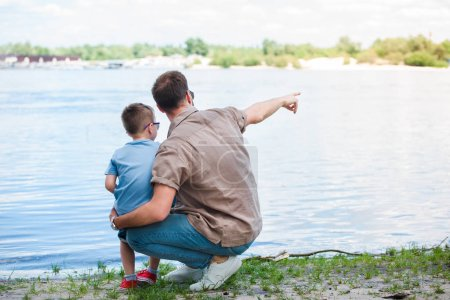 back view of father pointing on something at river to son at park