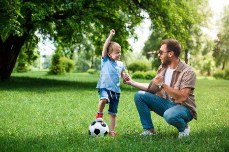 Photo pour Heureux père et fils montrant oui signe après avoir joué au football au parc - image libre de droit
