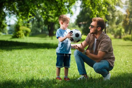 son giving football ball to father at park