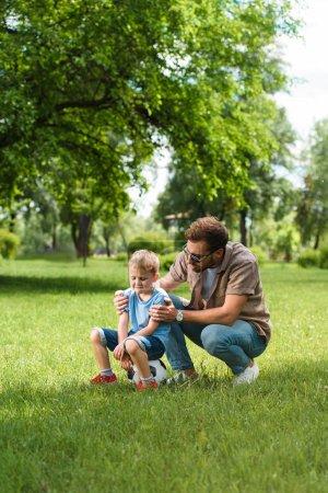 Photo pour Le père étreindre et soutenant les fils pleurant après jouer au football au parc - image libre de droit