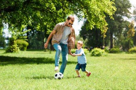 Photo pour Papa et fils jouant au football au parc - image libre de droit