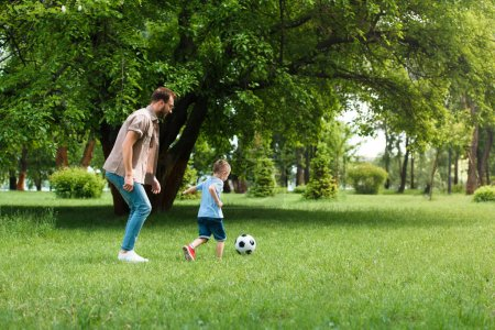 Photo for Side view of father and son playing football at park - Royalty Free Image