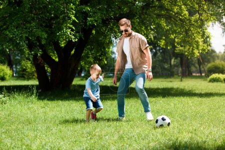father and son playing football on grass at park