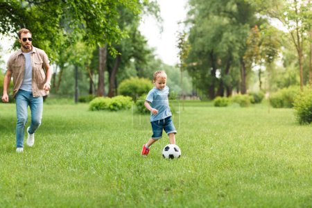 father and son playing football together at park