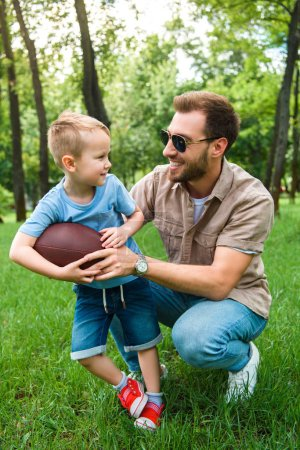 happy father and son with american football ball at park