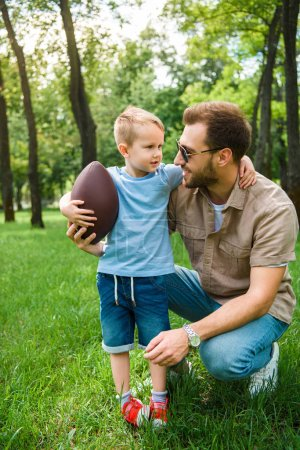 father and son hugging and holding american football ball at park