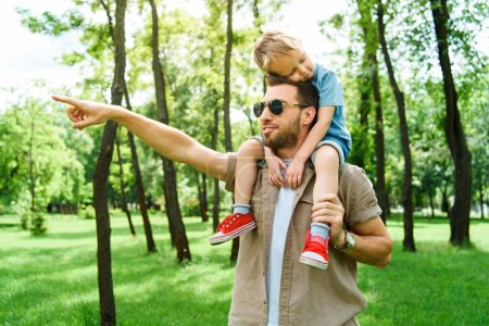 father pointing on something to son sitting on shoulders at park