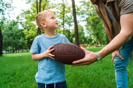 cropped image of father giving american football ball to son at park