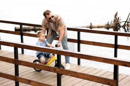 father teaching son riding bike on bridge near river