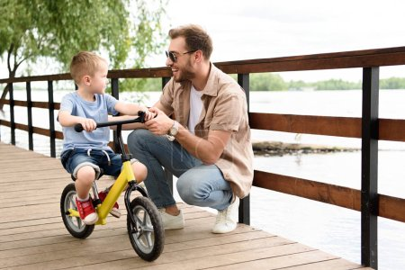 father teaching son riding bike on bridge at park