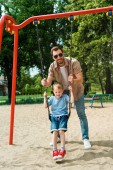 father and son having fun on swing at playground in park and looking at camera