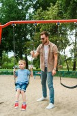 dad and son having fun on swing at playground in park
