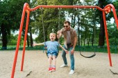 father and son having fun on swing at playground in park