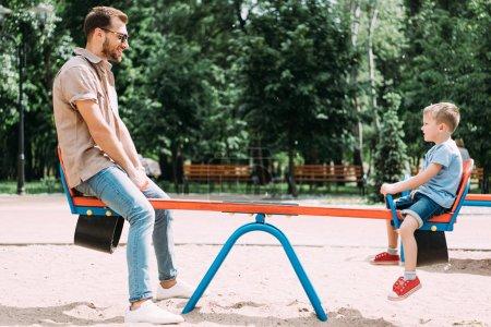 Photo pour Vue du côté du père et fils s'amuser sur swing au terrain de jeux dans le parc - image libre de droit