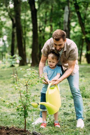 dad and son watering seedling with watering can at park