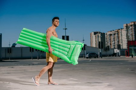 side view of young shirtless man with inflatable bed walking by parking