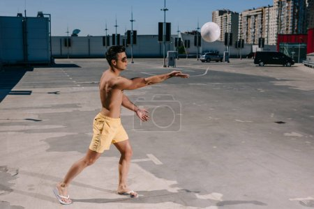 handsome young shirtless man playing beach volleyball on parking