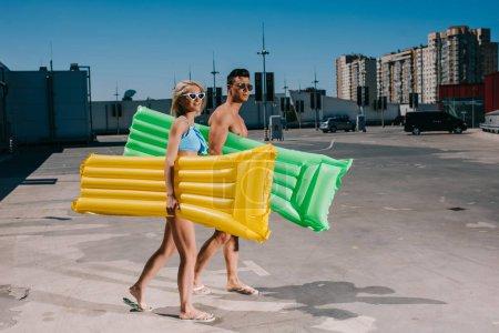 Photo pour Jeune couple en vêtements de plage avec lits gonflables marchant sur le parking - image libre de droit