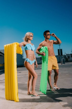 young couple in beach clothes with inflatable beds standing on parking