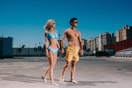 attractive young couple in beach clothes holding hands and walking on parking