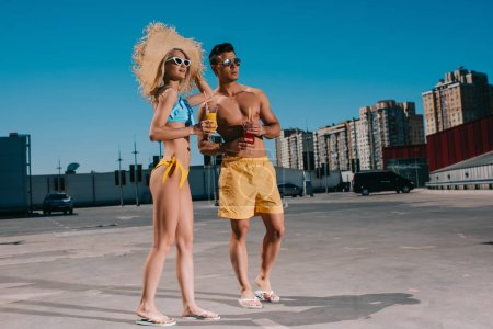 happy young couple in beach clothes with refreshing cocktails standing on parking