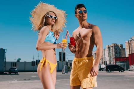 beautiful young couple in beach clothes with refreshing cocktails standing on parking