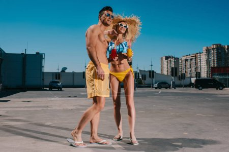 young couple in beach clothes with refreshing cocktails standing on parking