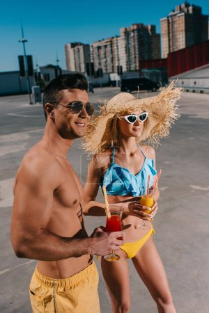 happy attractive couple in swimsuits with refreshing cocktails standing on parking