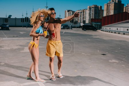 happy couple in swimsuits with refreshing cocktails standing on parking