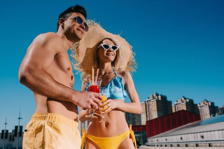 bottom view of young couple in swimsuits with refreshing cocktails in city