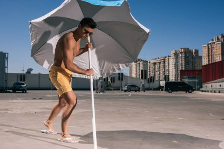 attractive young man putting beach umbrella in asphalt on parking