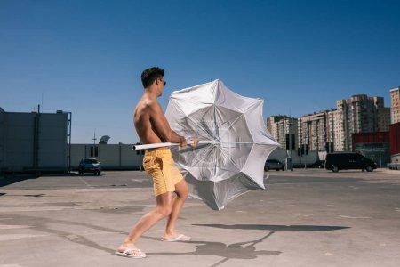 Photo pour Beau jeune homme torse nu avec parasol sur le parking - image libre de droit