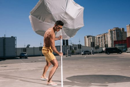 masculine young shirtless man putting beach umbrella in asphalt on parking