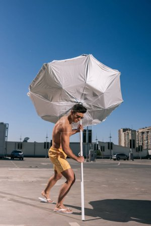 athletic young shirtless man putting beach umbrella in asphalt on parking