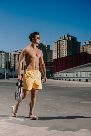 athletic young shirtless man with flippers on parking