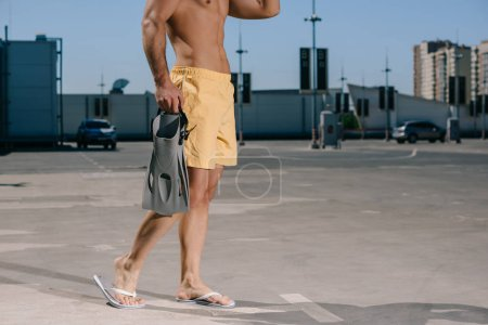 cropped shot of shirtless man in swimming shorts with flippers on parking
