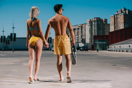 rear view of young couple in bikini and swimming shorts with flippers walking on parking