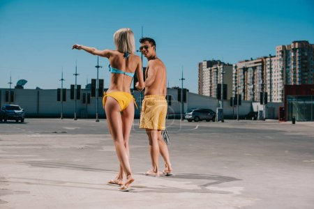 rear view of young attractive couple in bikini and swimming shorts pointing somewhere on parking