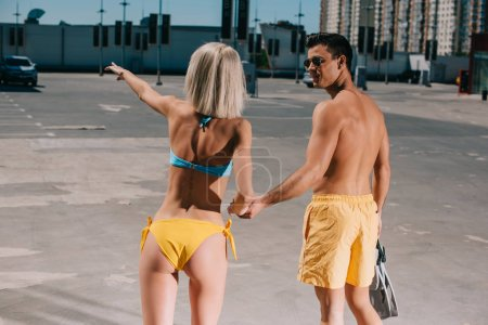 young couple in bikini and swimming shorts on parking