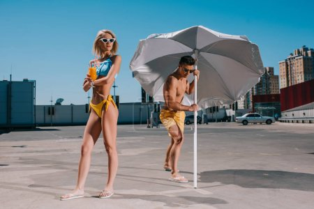 young attractive couple with umbrella in swimsuits tanning on parking